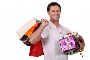 Smiling man with shopping bags and wrapped gifts
