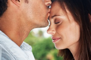 Closeup portrait of a young man kissing his cute girlfriend on forehead - Outdoor